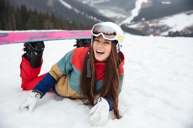 Молодая смеющаяся сноубордистка лежит на склонах морозным зимним днем