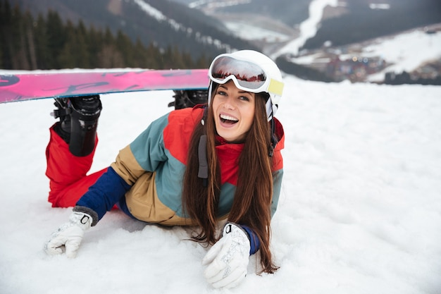 Young laughing lady snowboarder lies on the slopes frosty winter day