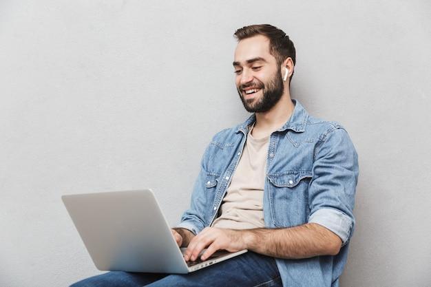 Молодой смеющийся человек с бородой печатает ноутбук и использует наушник, сидя на стуле, изолированном над серой стеной