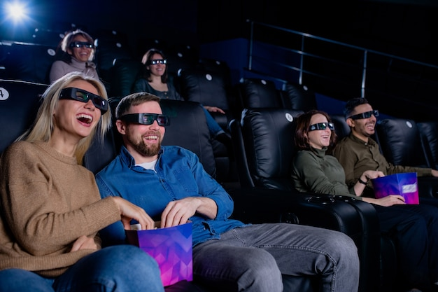 Young laughing man and woman and their friends in 3d eyeglasses having popcorn and watching movie in cinema