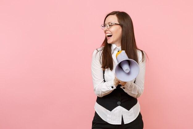 Молодой смех красивой деловой женщины в черном костюме, рубашке и очках, держа мегафон, глядя в сторону, изолированные на розовом фоне. леди босс. достижение карьерного богатства. скопируйте место для рекламы.