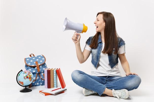 흰색 벽에 격리된 지구본, 배낭, 학교 책 근처에 앉아 있는 확성기를 들고 데님 옷을 입은 젊은 웃고 있는 예쁜 여학생