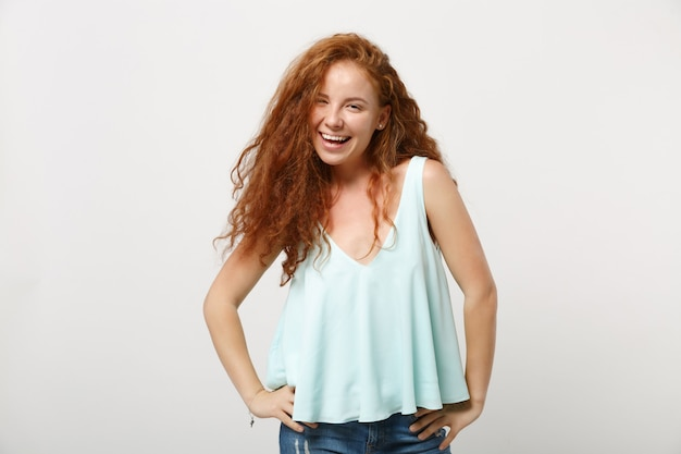 Young laughing redhead woman girl in casual light clothes posing isolated on white wall background, studio portrait. people lifestyle concept. mock up copy space. standing with arms akimbo on waist.