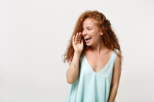 白い背景、スタジオの肖像画に分離されたポーズでカジュアルな明るい服を着た若い笑う赤毛の女性の女の子。人々のライフスタイルの概念。コピースペースをモックアップします。口の近くで手のジェスチャーで叫ぶ。