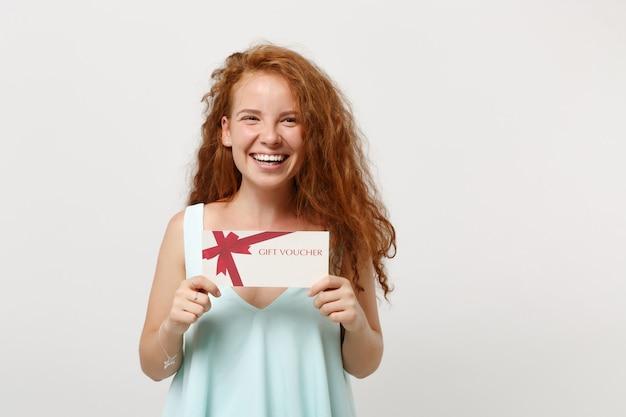 白い壁の背景、スタジオの肖像画に分離されたポーズでカジュアルな明るい服を着て若い笑う赤毛の女性の女の子。人々のライフスタイルの概念。コピースペースをモックアップします。手にギフト券を持っています。