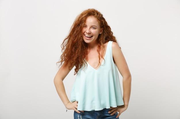 白い壁の背景、スタジオの肖像画に分離されたポーズでカジュアルな明るい服を着て若い笑う赤毛の女性の女の子。人々のライフスタイルの概念。コピースペースをモックアップします。腰に腕を腰に当てて立っている。