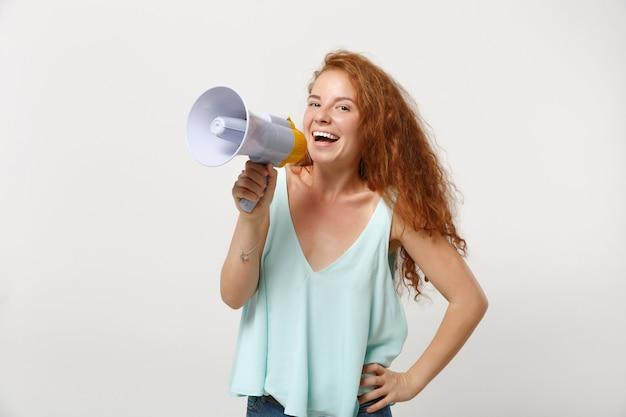 白い壁の背景、スタジオの肖像画に分離されたポーズでカジュアルな明るい服を着て若い笑う赤毛の女性の女の子。人々の誠実な感情のライフスタイルの概念。コピースペースをモックアップします。メガホンで叫ぶ。