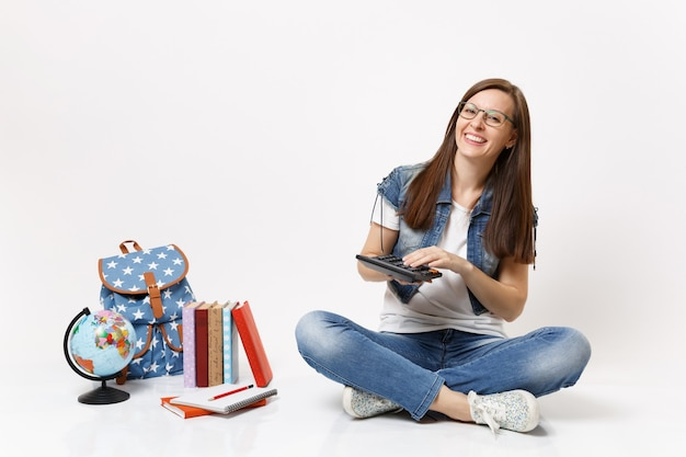 Молодой смеющийся умный студент-женщина держит и использует калькулятор, решающий математические уравнения, сидя рядом с земным шаром, рюкзаком, изолированными школьными учебниками