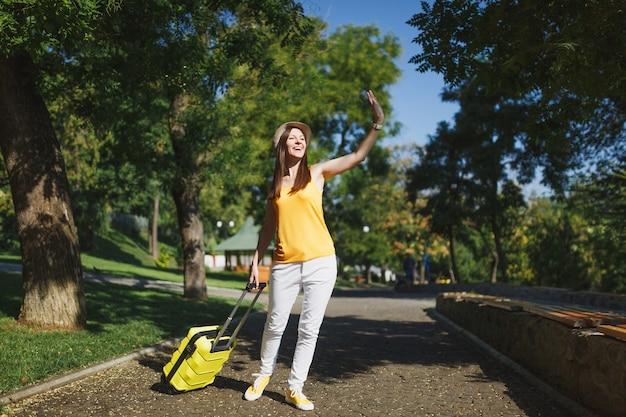 여행가방을 들고 모자를 쓰고 웃고 있는 젊은 여행자 관광 여성은 야외에서 친구를 만나기 위해 손을 흔들고 있습니다. 주말 휴가를 여행하기 위해 해외로 여행하는 소녀. 관광 여행 라이프 스타일.