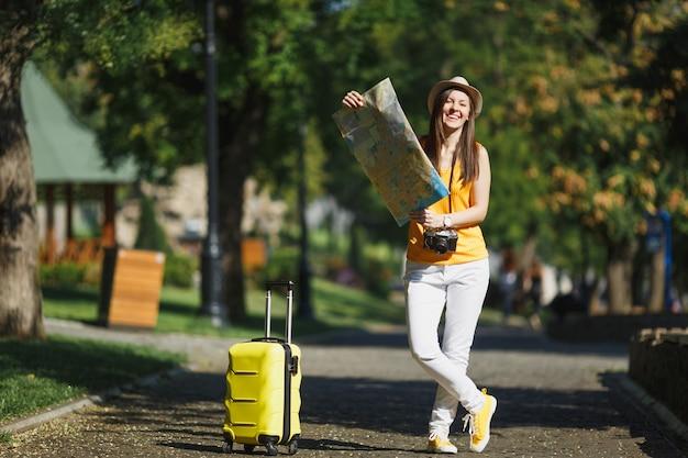 黄色の夏のカジュアルな服を着て、若い笑う旅行者の観光客の女性、スーツケースの都市地図の帽子は、街の屋外を歩きます。週末の休暇に旅行するために海外に旅行している女の子。観光の旅のライフスタイル。