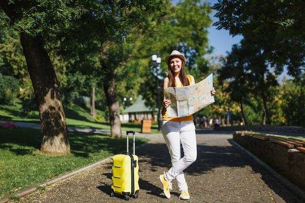노란색 여름 캐주얼 옷을 입고 웃고 있는 젊은 여행자 관광 여성, 여행 가방 도시 지도가 있는 모자는 도시 야외에서 산책합니다. 주말 휴가를 여행하기 위해 해외로 여행하는 소녀. 관광 여행 라이프 스타일.