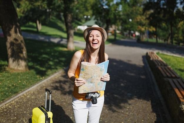 黄色の夏のカジュアルな服の帽子で若い笑う旅行者の観光客の女性は、屋外の都市の都市地図を保持しているスーツケースを持っています。週末の休暇で旅行するために海外旅行する女の子。観光の旅のライフスタイル。