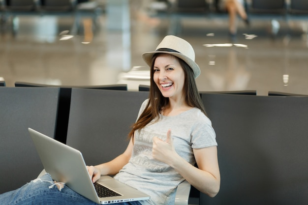 ノートパソコンで作業し、親指を立てて国際空港のロビーホールで待っている若い笑い旅行者観光客の女性