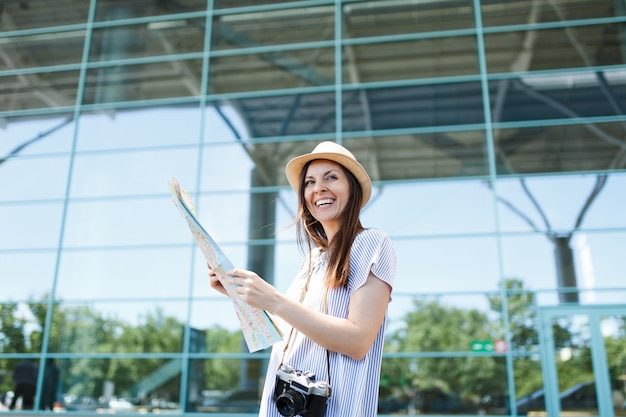 Giovane donna turistica viaggiatrice ridente con macchina fotografica vintage retrò che tiene mappa cartacea all'aeroporto internazionale