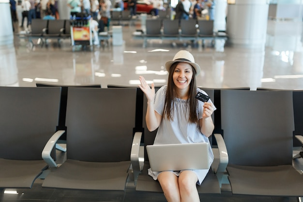 Молодой смеющийся путешественник турист женщина, работающая на ноутбуке, держит кредитную карту, раскинув руки, ждет в холле вестибюля в международном аэропорту