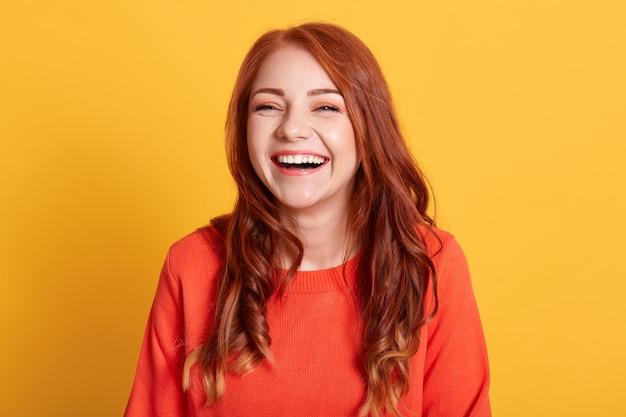Молодая смеющаяся женщина на желтом фоне выглядит счастливой, носит оранжевый свитер, выражает положительные эмоции, имеет рыжие волосы, находится в хорошем настроении.