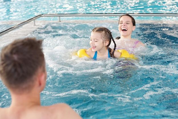 Молодая смеющаяся женщина и ее веселая маленькая дочь плавают в голубой чистой воде спа-бассейна, двигаясь к мужчине в центре курорта