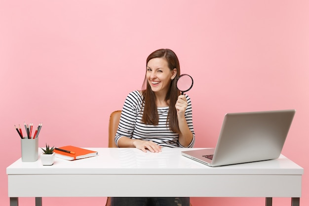 Young laughing woman in casual clothes holding magnifying glass sit working on project at white desk with pc laptop