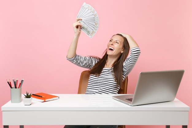 Young laughing woman clinging to head holding bundle lots of dollars, cash money working at office at white desk with pc laptop