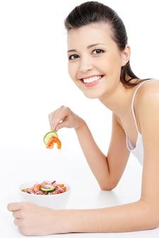Giovane donna che ride che mangia insalata sana - isolata su bianco