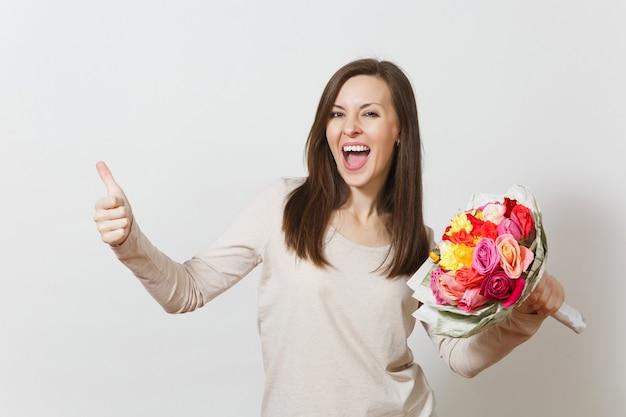 아름 다운 장미 꽃의 꽃다발을 들고 젊은 웃는 여자, 흰색 배경에 고립 된 엄지손가락을 보여줍니다. 광고 공간을 복사합니다. 성 발렌타인 데이 또는 국제 여성의 날 개념.