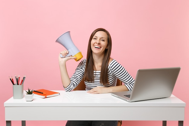 パステルピンクの背景に分離されたpcラップトップでオフィスの白い机に座ってプロジェクトに取り組んでいる間メガホンを保持している若い笑う女性。業績ビジネスキャリアコンセプト。スペースをコピーします。