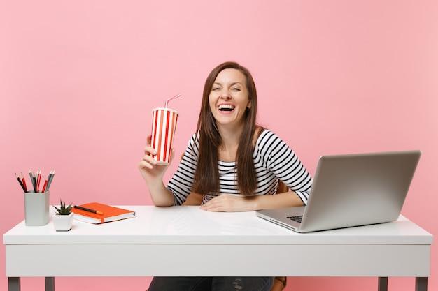 Молодая смеющаяся женщина, держащая пластиковую чашку с колой или содовой, сидит и работает за белым столом с современным ноутбуком