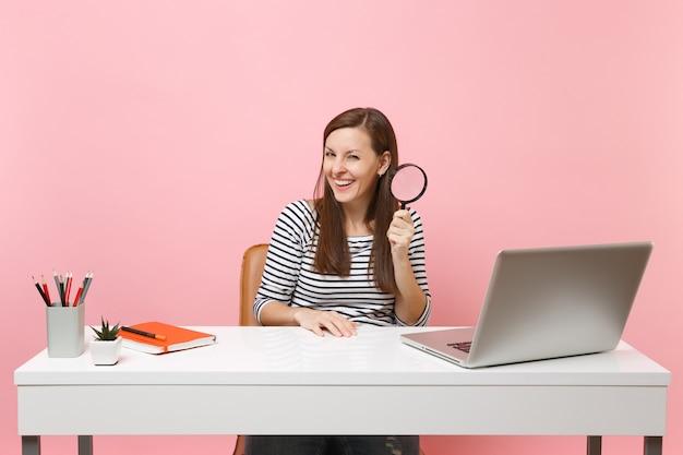 돋보기를 들고 평상복을 입은 젊은 웃고 있는 여성은 파스텔 핑크색 배경에 격리된 pc 노트북이 있는 흰색 책상에 앉아 프로젝트를 진행하고 있습니다. 성취 비즈니스 경력 개념입니다. 공간을 복사합니다.