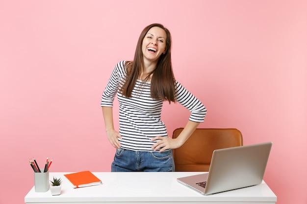パステルピンクの背景に分離された現代的なpcのラップトップと白い机の近くに立って、カジュアルな服を着て笑っている若い女性が働いています。業績ビジネスキャリアコンセプト。広告用のスペースをコピーします。