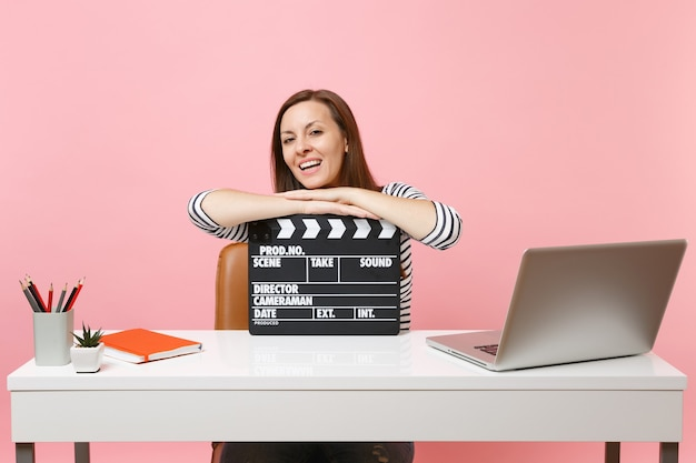 Young laughing woman leaning on classic black film making clapperboard and working on project while sitting at office with laptop isolated on pink background. achievement business career. copy space.