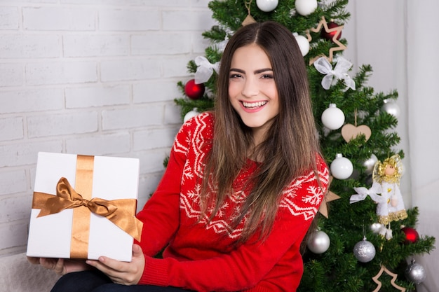 Young laughing woman opening gift box near decorated christmas tree
