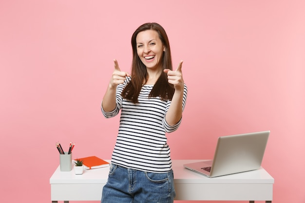 人差し指を前に向けて笑っている若い女性。ノートパソコンで白い机の近くに立って仕事