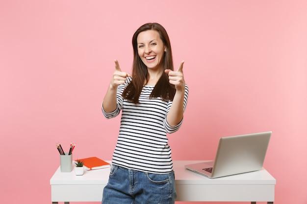 パステルピンクの背景で隔離のラップトップと白い机の近くに立っているカメラワークに人差し指を指している若い笑う女性。業績ビジネスキャリアコンセプト。広告用のスペースをコピーします。