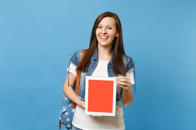Young laughing woman student in denim clothes with backpack holding tablet pc computer with blank black empty screen isolated on blue background. education in college. copy space for advertisement.