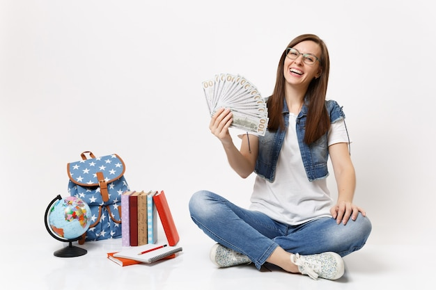 Young laughing woman student in glasses holding bundle lots of dollars, cash money sitting near globe, backpack, school books isolated