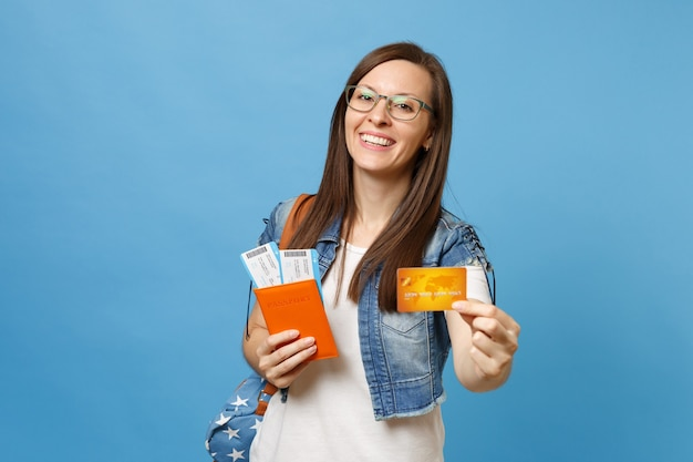Young laughing woman student in glasses with backpack holding passport boarding pass tickets credit card isolated on blue background. education in university college abroad. air travel flight concept.