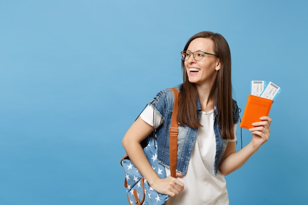 Young laughing woman student in glasses with backpack looking aside hold passport, boarding pass tickets isolated on blue background. education in university college abroad. air travel flight concept.