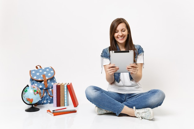 Young laughing woman student holding using tablet pc computer, making video call, sitting near globe, backpack, school books isolated on white wall