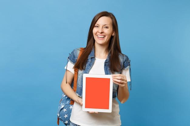 Молодой смеющийся студент женщины в джинсовой одежде с рюкзаком, держащим планшетный компьютер с пустым черным пустым экраном, изолированным на синем фоне. обучение в колледже. скопируйте место для рекламы.