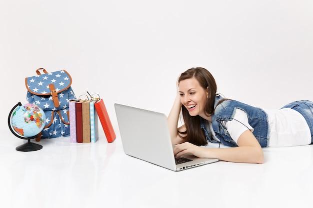 Молодая смеющаяся студентка в джинсовой одежде, работающая на портативном компьютере, лежащем рядом с земным шаром, рюкзаком, изолированными школьными учебниками