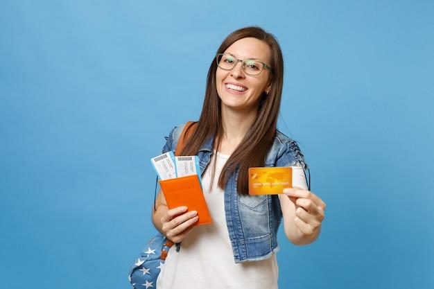 Молодой смеющийся студент женщины в очках с рюкзаком, держащим кредитную карту билетов на посадочный талон паспорта, изолированную на синем фоне. обучение в вузе за рубежом. концепция полета авиаперелета.