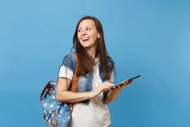 흰색 티셔츠를 입은 젊은 여성 학생, 파란색 배경에 격리된 채로 태블릿 pc 컴퓨터를 들고 배낭을 메고 데님 옷을 입고 있습니다. 대학에서 교육입니다. 광고 공간을 복사합니다.