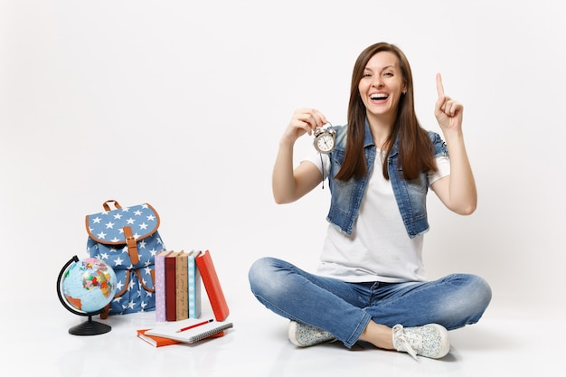 Young laughing woman student pointing index finger up holding alarm clock sitting near globe, backpack, school books