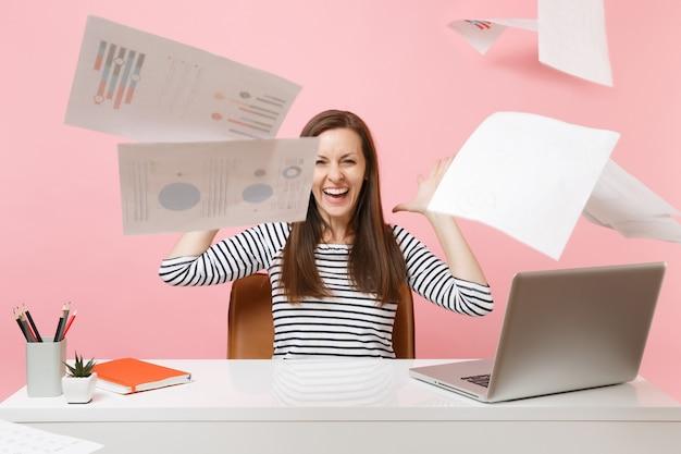 プロジェクトに取り組んでいる間、週末の前にラップトップを持ってオフィスに座って、紙の文書を投げる若い笑う女性