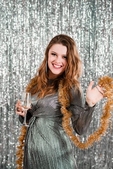 Young laughingwoman with glass near tinsel