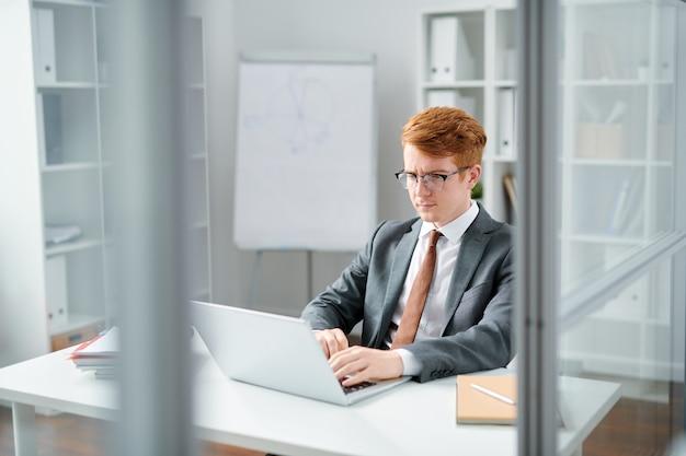 オンラインデータの読み取りに集中しながらノートパソコンのディスプレイを見ているエレガントなスーツを着た若い弁護士