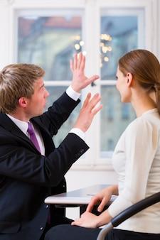 彼のオフィスで働いており、女性の顧客またはクライアントと相談している若い弁護士、保険代理店または弁護士