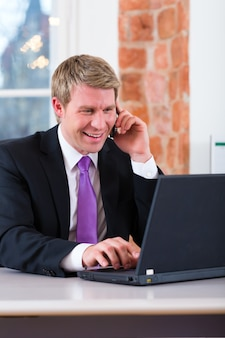 사무실에서 일하는 젊은 변호사, 그는 책상에 앉아 전화로 고객 또는 고객입니다.