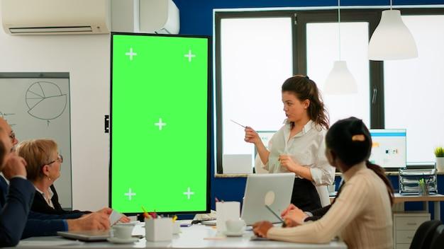 젊은 리더는 회의 테이블 앞에 서서 재무 통계를 분석하고 그린스크린 디스플레이를 보고 다양한 비즈니스 팀에 대해 설명합니다. 크로마 키 데스크탑에서 프로젝트를 계획하는 다민족 근로자