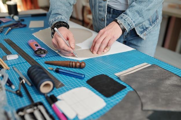 白いスエードの部分の上に型紙の輪郭を描きながらテーブルの上に曲がるデニムの作業服の若い革細工人